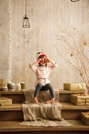 Stylish little girl in light pink dress sits in the christmas decorations, dressed in funny hat