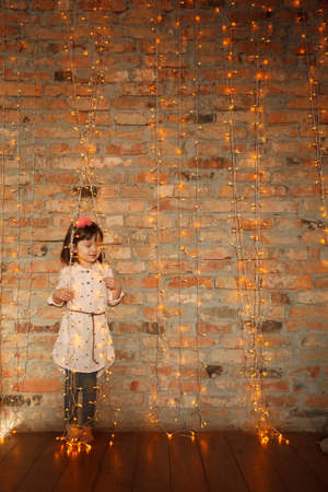 Stylish little girl in light pink dress with lighting christmas string