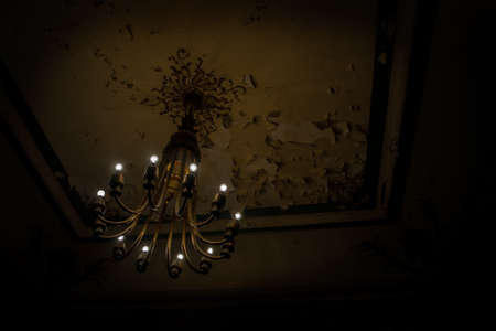 Interior scene of a chandelier in a grungy and dark concrete wasted room. Stock Photo - 23082757