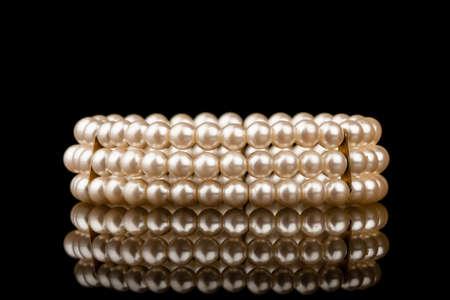 Pearl bracelet with refelction on black backgrund photo