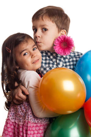 boy giving kiss to girl with flowers and balloons on white background photo