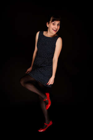 stylish expressive woman with red shoes on black background