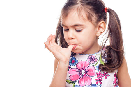 young girl on white background licking finger Stock Photo