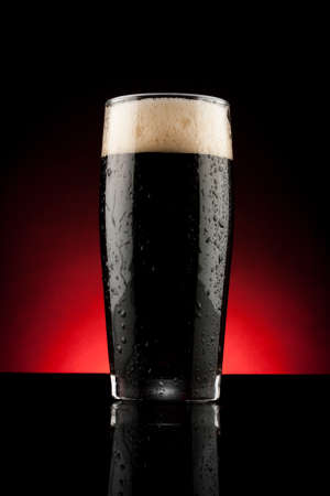 glass of black beer with reflection and water drops photo