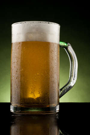 back lit glass mug with beer with reflection photo