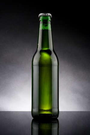 studio shot of back lit green beer bottle photo
