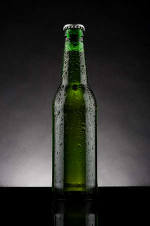 back lit green beer bottle with water drops photo