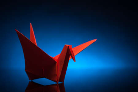 red origami paper crane with blue back light photo