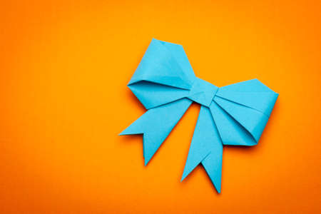 blue origami paper bow on orange paper background photo