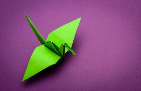 green origami paper crane on purple paper background photo