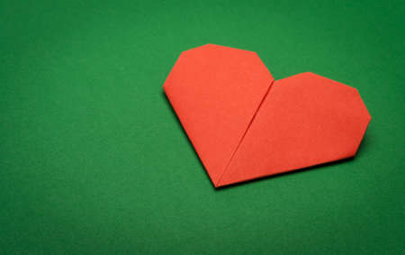 red origami paper heart on green paper background photo