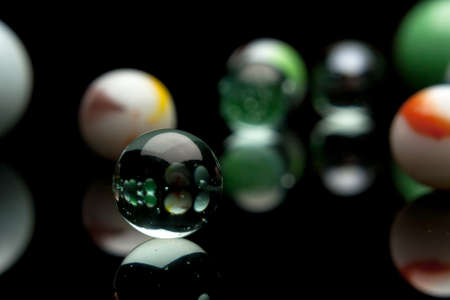 photo of color marbles on black with reflection photo