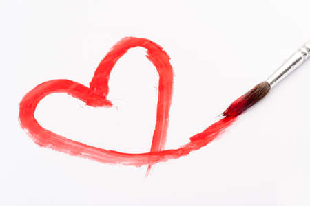 paint brush with red heart painted on white paper photo