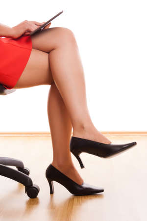businesswoman legs with tablet and red office dress photo