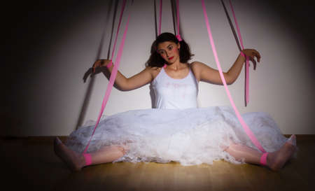 woman portraid as a marionette puppet controlled by strings