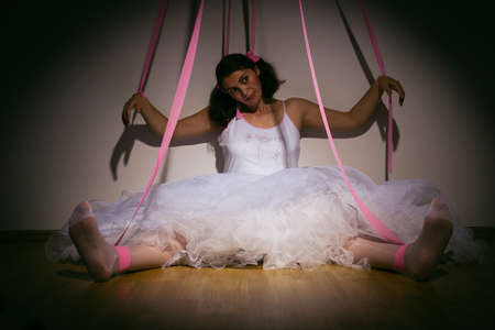 manipulate: woman portraid as a marionette puppet controlled by strings