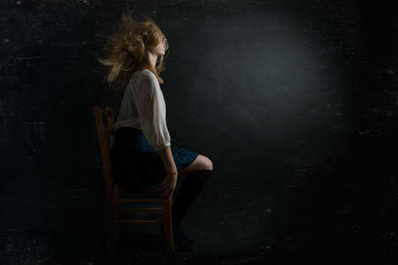 dark photo of a girl on a chair with flying hair photo