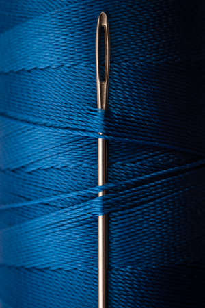 close up of a sewing needle head and blue thread photo