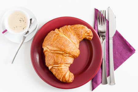 croissant on marsala color plate with napkin, knife, fork and coffee on white table photo