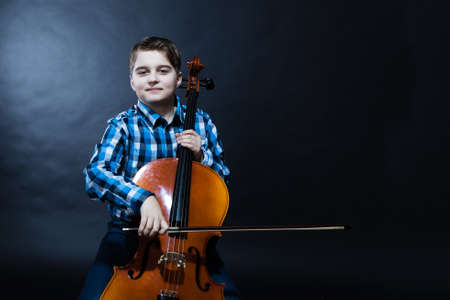 young boy Cellist playing classical music on cello Stock Photo
