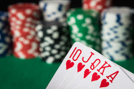 straight flush: hearts straight flush with poker chips on green table
