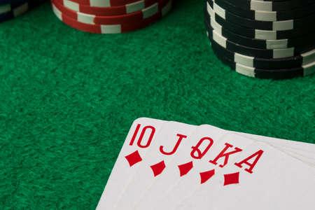 straight flush: diamonds straight flush with poker chips on green table Stock Photo