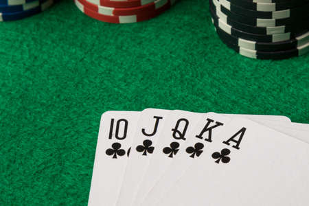 straight flush: clubs straight flush with poker chips on green table Stock Photo