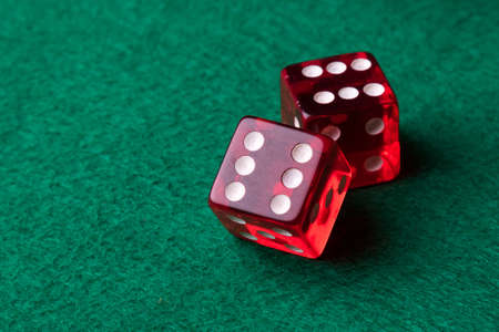 two red casino dices on green table photo