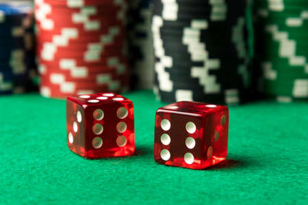 red casino dices and poker chips on green table