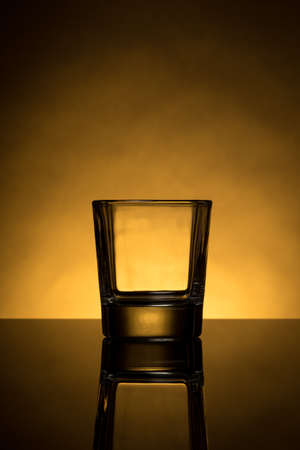 one back lit empty whiskey glass with reflection photo