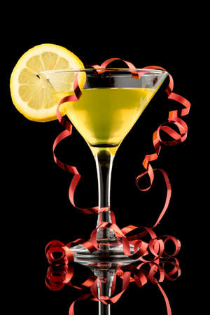 lemon martini on black with red party streamer photo