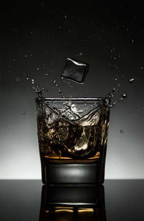 splashing whiskey with ice cubes and reflection photo