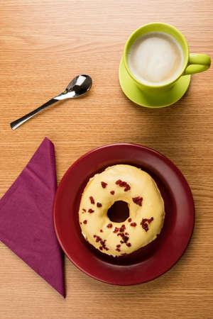 fresh doughnut on a marsala plate and coffee on table photo
