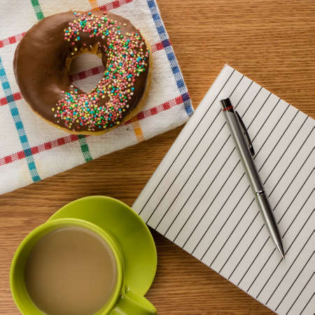 doughnut coffee and notepad with pen on a table photo