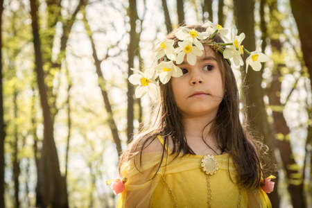 queen of angels: little girl in yellow princess dress in forest Stock Photo