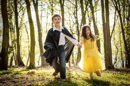 queen's theatre: boy with black cape and girl in yellow princess dress in forest Stock Photo