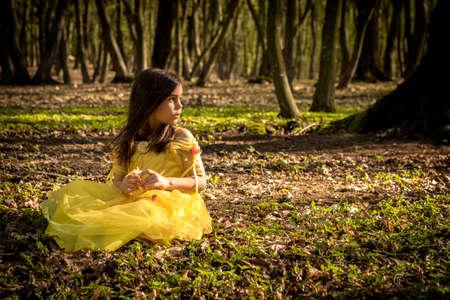 princesa: niña en el vestido de la princesa de color amarillo en el bosque Foto de archivo