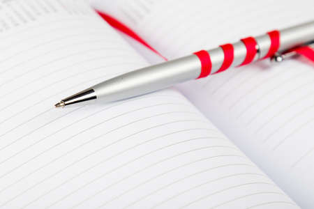 silver pen on opened notebook with red string photo