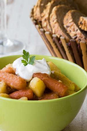 goulash: potato and carrot goulash in a green bowl Stock Photo