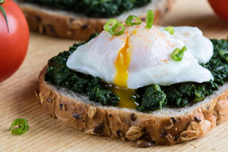 flavorsome: Poached egg on a piece of brown bread with spinach on a wooden table Stock Photo