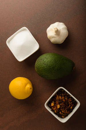 condiments: fresh healthy green avocado fruit with lemon, onion and condiments