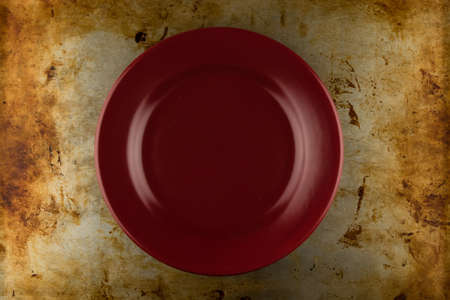 grunge flatware: empty red shiny plate on grungy metal background