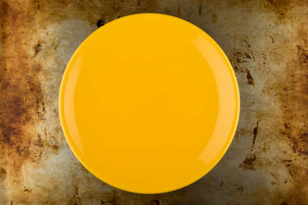 grunge flatware: empty yellow shiny plate on grungy metal background