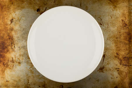 grunge flatware: empty white shiny plate on grungy metal background