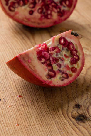 juicy: fresh juicy cut pomegranate on wooden table
