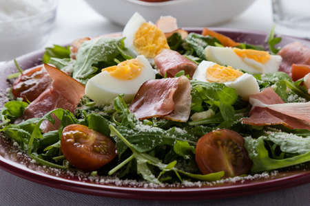 rucola: rucola salad with ham, cheese and tomatoes Stock Photo