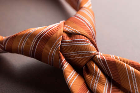casual wear: elegant casual orange neck tie knot on table Stock Photo