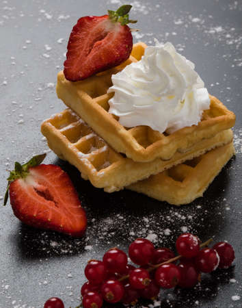 sugary: waffle with currant and strawberry on black sugary table Stock Photo