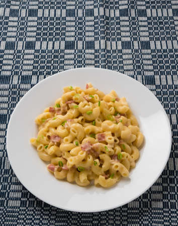 fresh tasty macaroni and cheese on white plate on blue table cloth Stockfoto