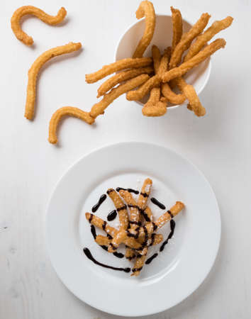 churros: homemade fried churros dessert on white plate with chocolate Stock Photo
